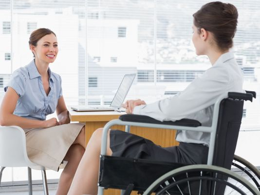 Businesswoman speaking with woman with disability